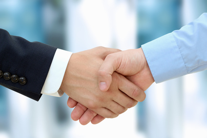 Close-up image of a firm handshake  between two colleagues in office.